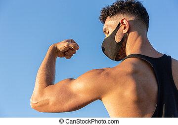 二頭筋, 青い空, coronavirus., コピー, covid-19, 彼の, スペース, に対して, マスク, バックグラウンド。, 身に着けていること, 顔, 運動, 人, 概念, 提示, コーカサス人, 戦い