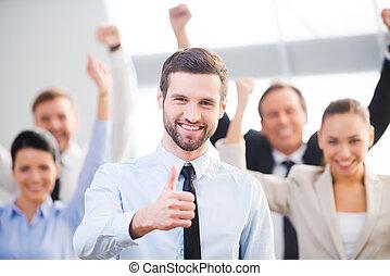 確信した, 感じ, ビジネスマン, の上, 幸せ, 背景, 親指, team., 提示, 微笑に立つこと, 彼の, 同僚, 間